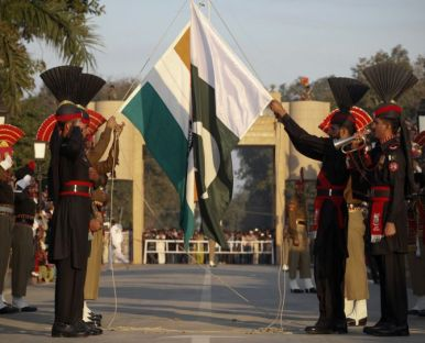 Pakistan Rangers (R) and Indian Border Security Force personnel take part in the daily flag lowering ceremony at their joint border post of Wagah near Lahore February 10, 2011. Nuclear-armed Pakistan and India have agreed to resume their official dialogue broken off after the 2008 attack on the Indian city of Mumbai, the Pakistani foreign ministry said on Thursday. REUTERS/Mohsin Raza (PAKISTAN - Tags: POLITICS MILITARY) - RTXXOU3